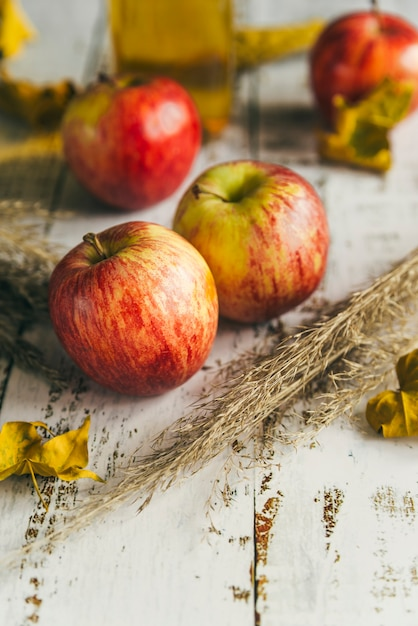 Apples with dry leaves on shabby table Free Photo