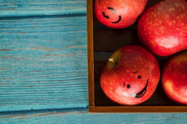 Apples with funny faces in wooden box Free Photo