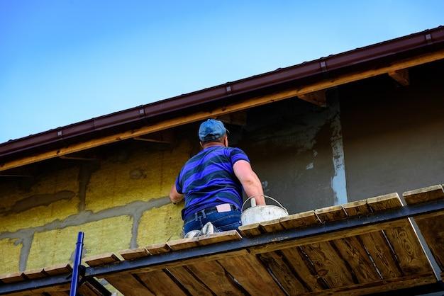 Нанесение слоя строительного клея на утепленную стену для покрытия стеклопластиковой арматурной сетки на минеральной вате. Premium Фотографии