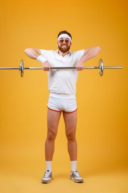 Il giovane sportivo appy fa gli esercizi di sport con il bilanciere Foto Gratuite