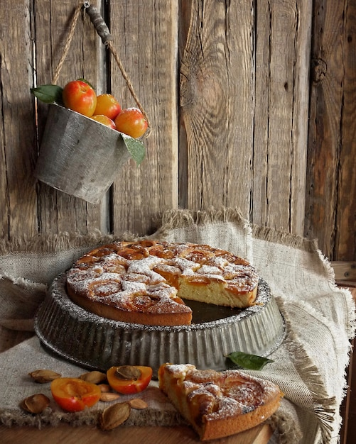 Apricot cake on vintage form on the old wooden walls. vintage bucket with fresh apricots Premium Photo