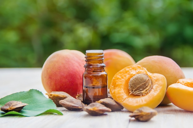Apricot oil in a small jar. selective focus. Premium Photo