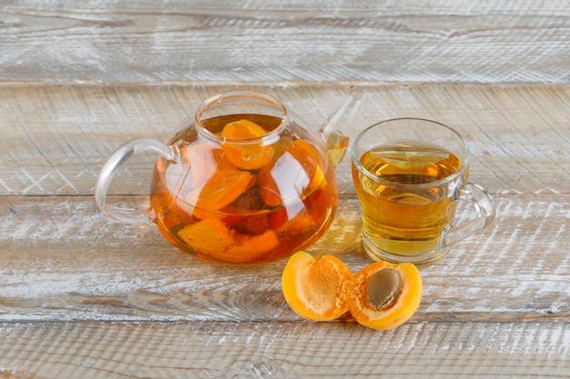 Абрикосовый чай в чайнике и стеклянная кружка с абрикосами сверху на деревянном столе Бесплатные Фотографии