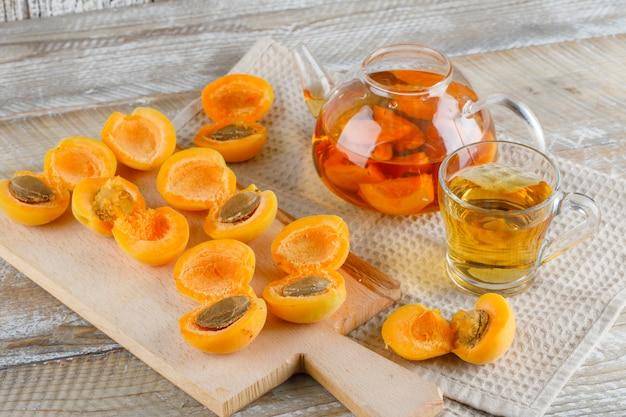 Абрикосовый чай в чайнике и кружка с абрикосами, разделочная доска сверху на деревянном и кухонном полотенце Бесплатные Фотографии