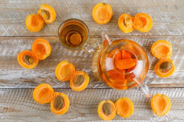 Абрикосовый чай с абрикосами в чайнике и стеклянная кружка на деревянном столе, плоская планировка. Бесплатные Фотографии
