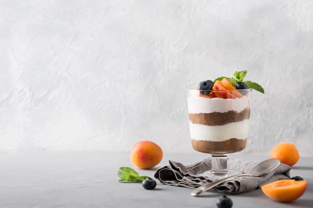 Apricot trifle, chocolate biscuit, layered dessert with  berry and  cream cheese on grey. Premium Photo