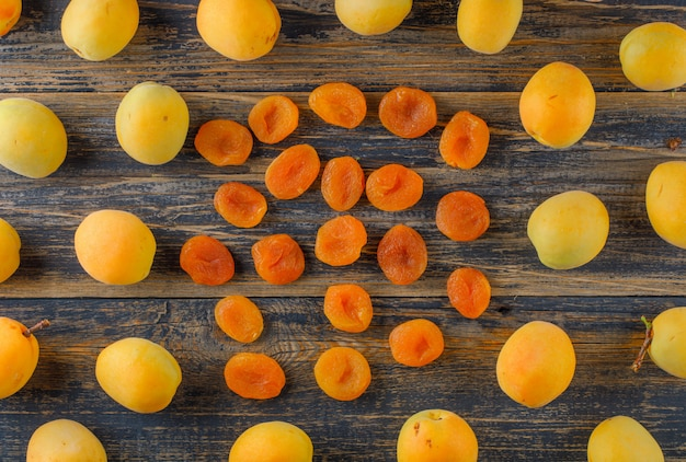 Apricots with dried apricots on wooden table, flat lay. Free Photo