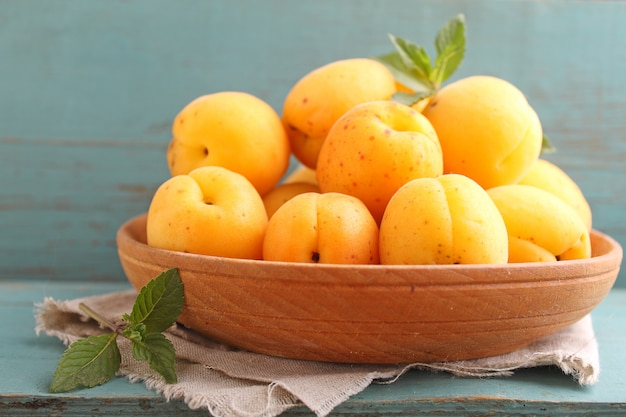 Apricots in a wooden plate with mint leaves Premium Photo