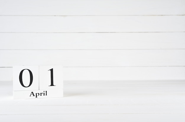April 1st, day 1 of month, birthday, anniversary, wooden block calendar on white wooden background with copy space for text. Premium Photo
