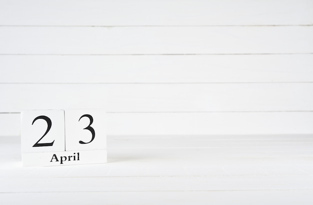 April 23rd, day 23 of month, birthday, anniversary, wooden block calendar on white wooden background with copy space for text. Premium Photo