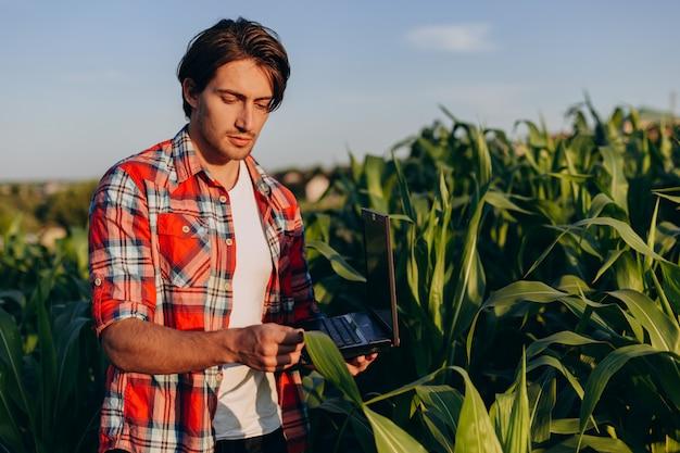 農学者が収穫を管理し、ラップトップで植物を尊重しているarフィールドに立っています。 Premium写真