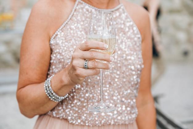 輝くピンクのドレスを着た女性は彼女のarでシャンパングラスを保持します。 無料写真
