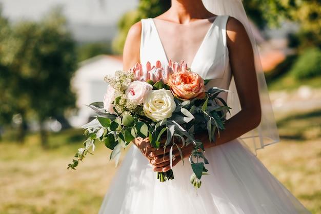 花嫁の散歩。古典的なドレスの美しい花嫁はarと歩く 無料写真