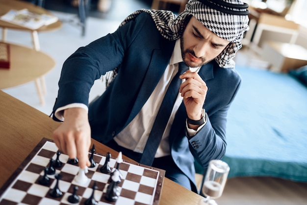 Arab businessman playing chess at table at hotel room. Premium Photo