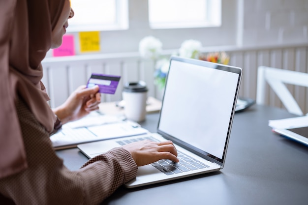 Arab businesswoman brown hijab shop online with a purple credit card on mockup white screen laptop at home. Premium Photo