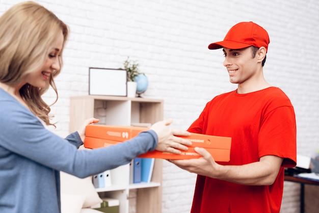 Arab deliveryman gives pizza box smiling girl. Premium Photo