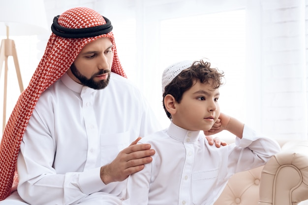 Arab man asks for forgiveness from small offended son. Premium Photo