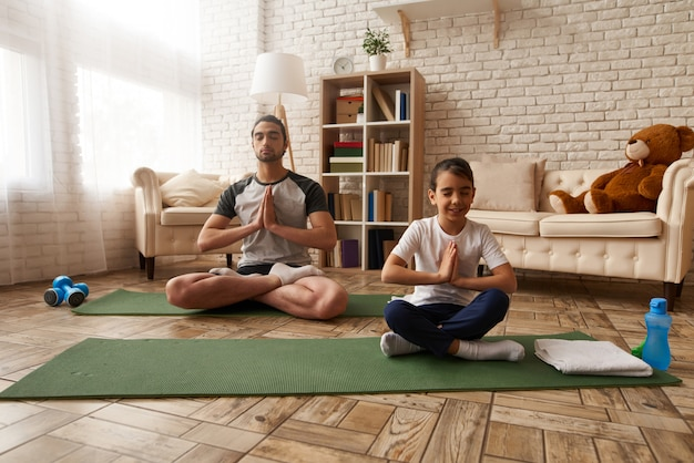 Arab man and girl are doing exercises at home Premium Photo