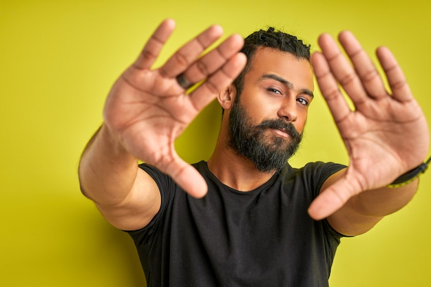 Arab man is making frame with hands and fingers with confident face, young male Premium Photo