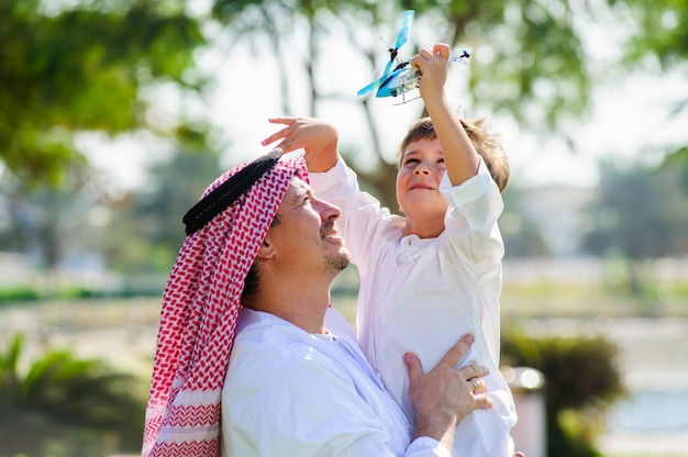 Arab man in traditional dress holds his son and play with toy plane. Premium Photo
