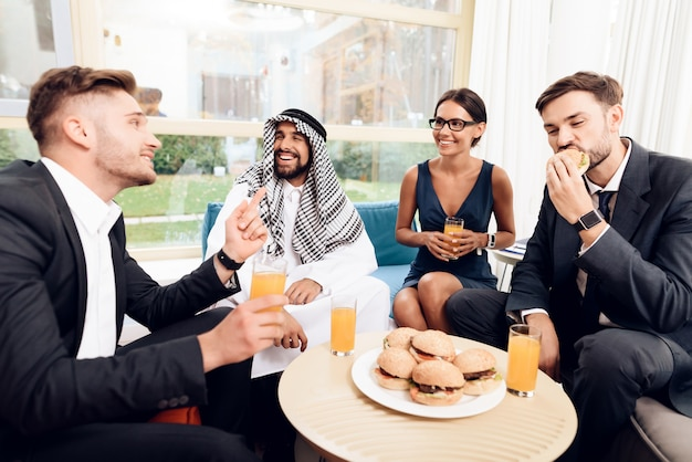 Arab and other businessmen are eating burgers. Premium Photo