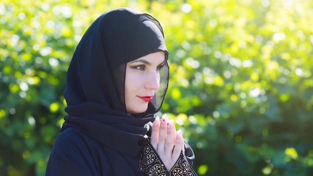 黒い服を着たアラブの女性は、背景の緑の木々に対して神に祈っています。 Premium写真