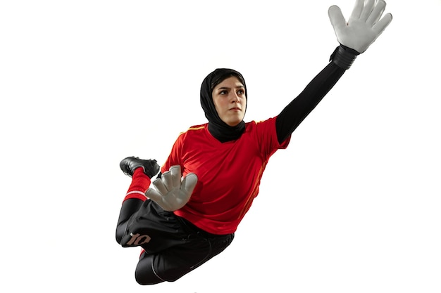 アラビアの女性サッカーまたはサッカー選手、白いスタジオの背景にゴールキーパー。ボールをキャッチし、トレーニングし、動きと行動の目標を保護する若い女性。 無料写真