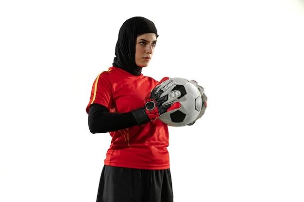 アラビアの女性サッカーまたはサッカー選手、白いスタジオの背景にゴールキーパー。ボールに自信を持ってポーズをとって、チームの目標を守る若い女性。 無料写真