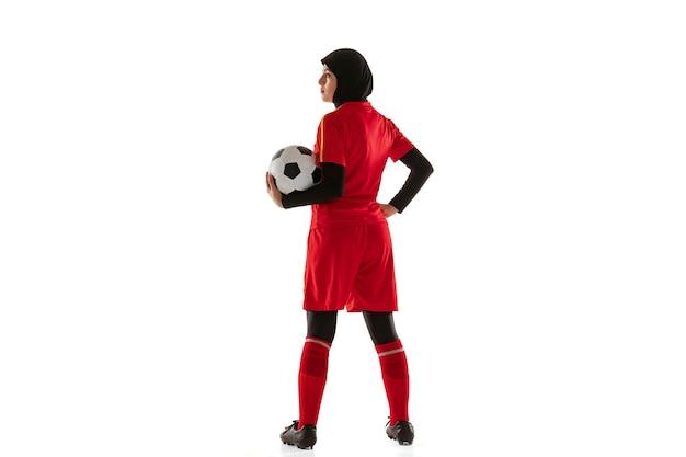 白いスタジオの背景に分離されたアラビアの女性サッカーまたはサッカー選手。ボールを持って、トレーニングし、動きと行動で練習している若い女性。 無料写真