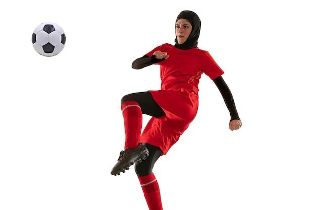아라비아 여성 축구 또는 축구 선수 흰색 스튜디오 배경에 고립. 공을 차고, 훈련, 모션 및 행동 연습 젊은 여자. 무료 사진