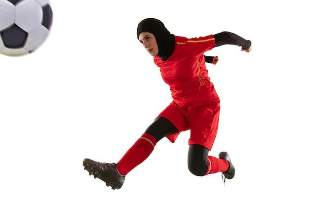 白いスタジオの背景に分離されたアラビアの女性サッカーまたはサッカー選手。ボールを蹴り、トレーニングし、動きと行動の練習をしている若い女性。 無料写真