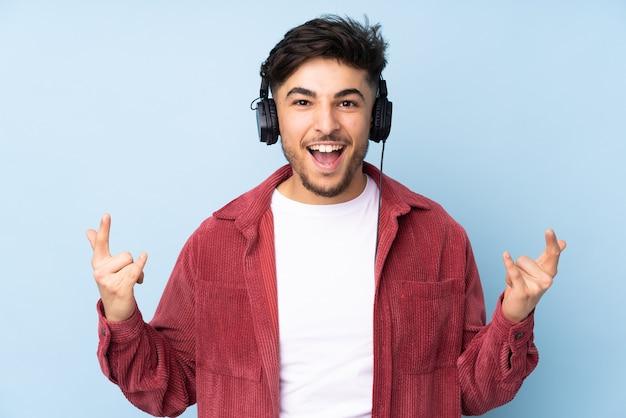 アラビアの男がロックジェスチャーを作る音楽を聴く Premium写真