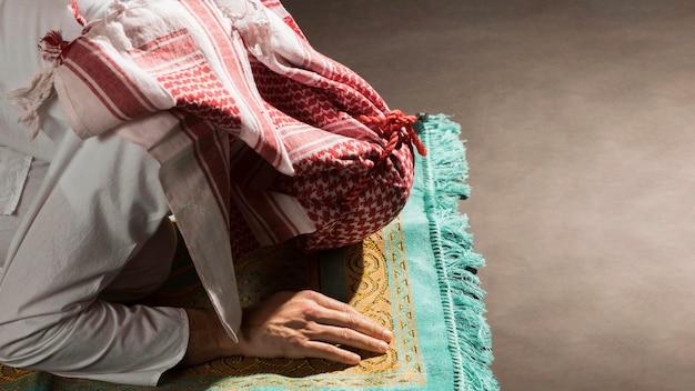Arabian man with kandora bow on prayer rug Free Photo