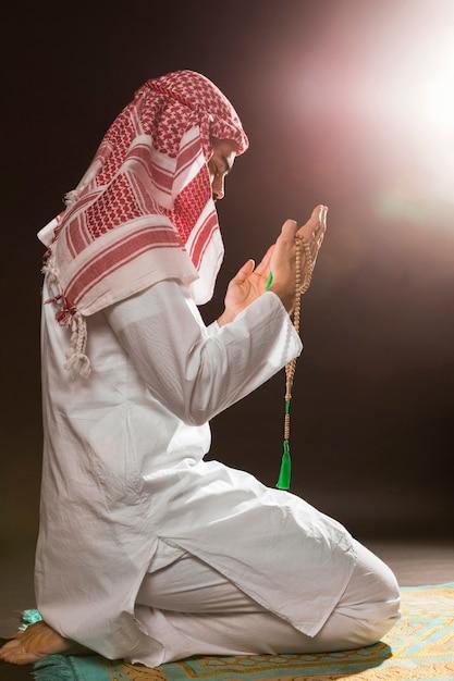 Arabian man with kandora praying and holding prayer beads Free Photo