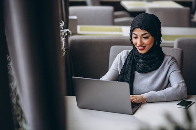 Arabian woman in hijab inside a cafe working on laptop Free Photo