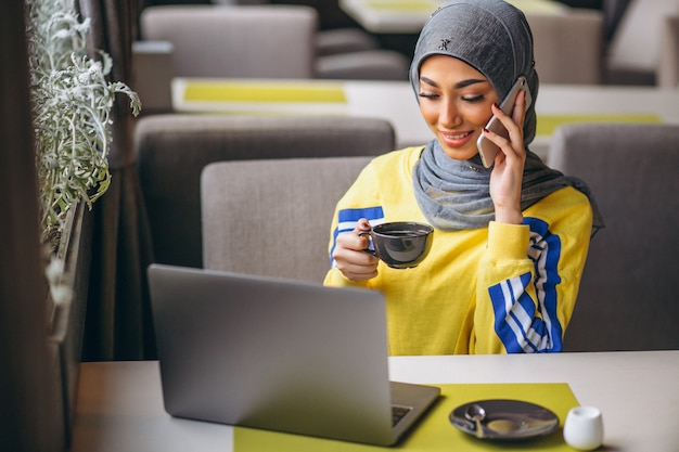 Arabian woman in hijab inside a cafe working on laptop Free Photo