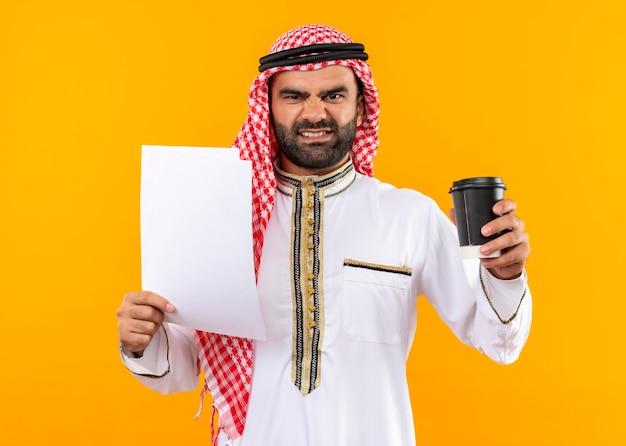 オレンジ色の壁の上に立っている怒っている顔と伝統的なウェアホールディングドキュメントとコーヒーカップのアラビアのビジネスマン 無料写真