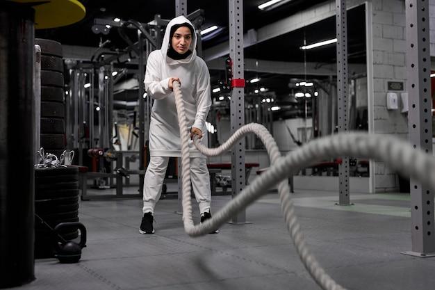 スポーティーなヒジャーブを身に着けて、バトルロープでクロスフィットトレーニングをしているアラビアの女性アスリート。定期的なスポーツは免疫システムを高め、健康を促進します。健康的な生活様式 Premium写真