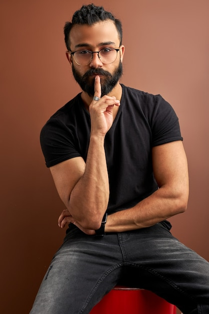 Arabic guy keep silence, isolated on brown studio background, handsome guy hold finger near mouth, look at camera Premium Photo