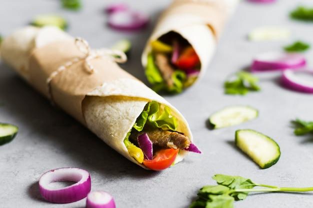 Arabic kebab sandwich wrapped in thin pita Free Photo