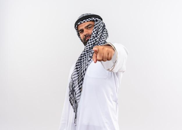 Арабский мужчина в традиционной одежде, уверенно улыбаясь, указывая указательным пальцем на белую стену Бесплатные Фотографии