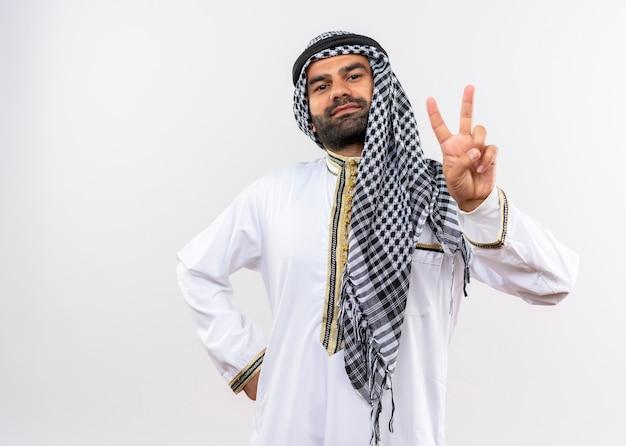 Арабский мужчина в традиционной одежде, уверенно улыбаясь, показывает знак победы, стоящий над белой стеной Бесплатные Фотографии