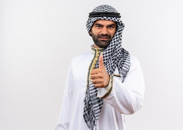 Арабский мужчина в традиционной одежде улыбается, показывает палец вверх, стоя над белой стеной Бесплатные Фотографии