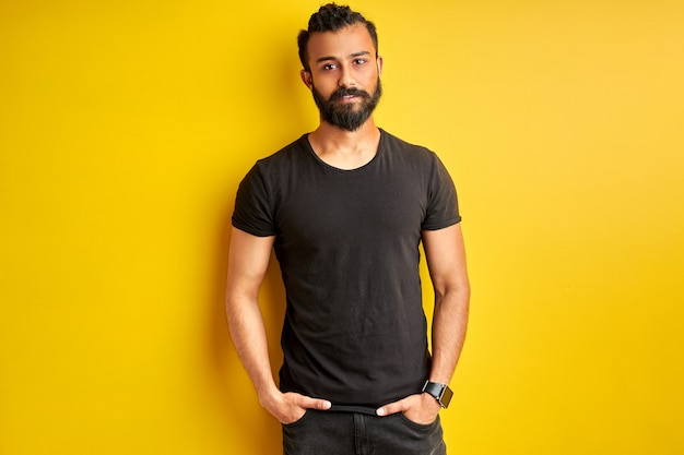 Arabic man with hands in pocket looks at camera, friendly guy posing Premium Photo
