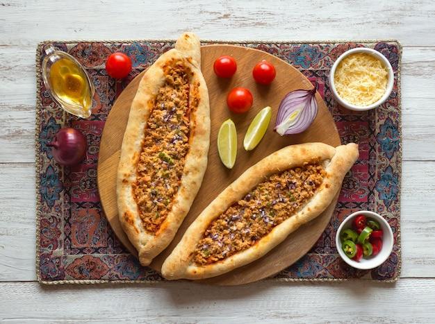 Арабская пицца lahmacun на белой деревянной поверхности Premium Фотографии