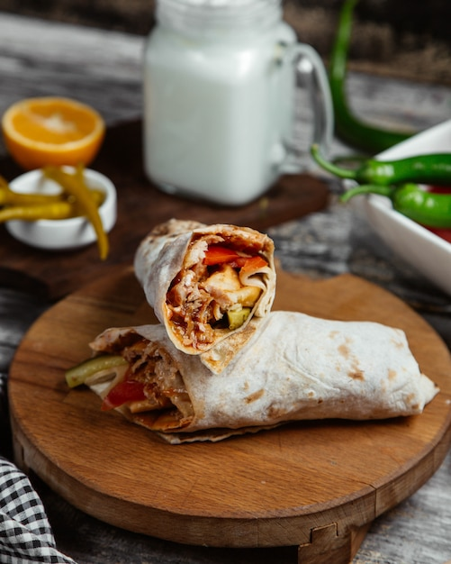 Arabic street food shaurma in lavash on a wooden platter. Free Photo