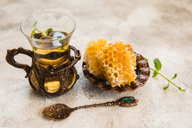 Arabic tea glass with honeycomb on table Free Photo