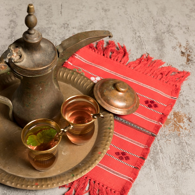 Arabic tea in glasses with teapot on cloth Free Photo