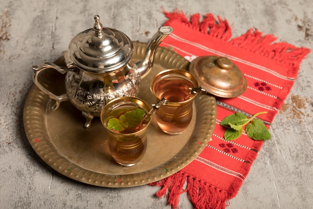 Arabic tea in glasses with teapot on red cloth Free Photo