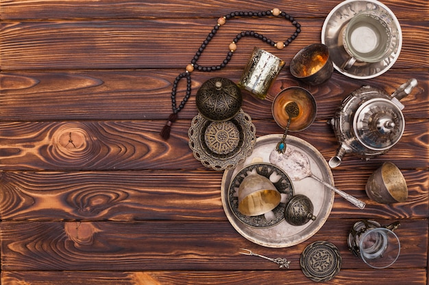 Arabic teapot with cups and beads on table Free Photo